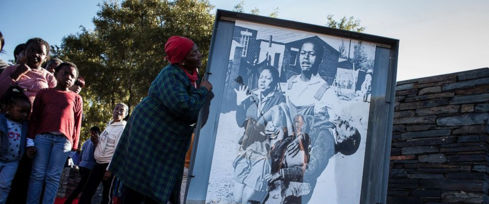 PHOTO: Ms. Nontsikelelo Makhubu is seen next to the iconic photograph showing Hector Pieterson being carried away during the start of the Soweto Uprising in 1976, during celebrations to commemorate the 40th anniversary.