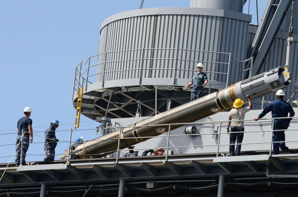 PHOTO: Sailors and civilian mariners assigned to the submarine tender USS Frank Cable (AS 40) raise a Tomahawk cruise missile before loading it onto a submarine.