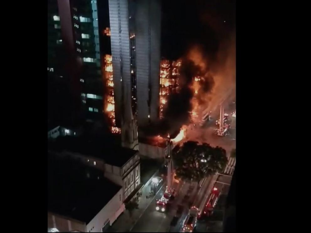 PHOTO: Video posted on social media early Tuesday showed a multi-story buildings crumbling upon itself as a fire raced towards the top floor.