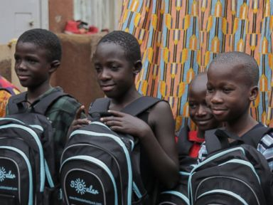PHOTO: Local children pose with solar panel equipped backpacks from the Soular Backpack that launched in 2015 to allow children take control of their education, Katwe, Uganda.