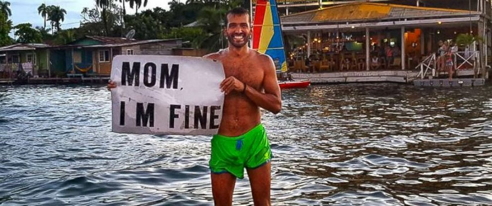 """PHOTO: Jonathan Quinonez travels the world and posts pictures holding a """"Mom Im Fine"""" sign to his Instagram account."""