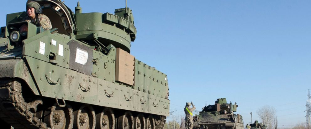 PHOTO:Soldiers, stationed at Fort Stewart, Ga., use proper hand signals to ground Bradley Fighting Vehicles onto the flatbeds of a train during a railhead operation near Smardan, Romania, Dec. 3, 2015.