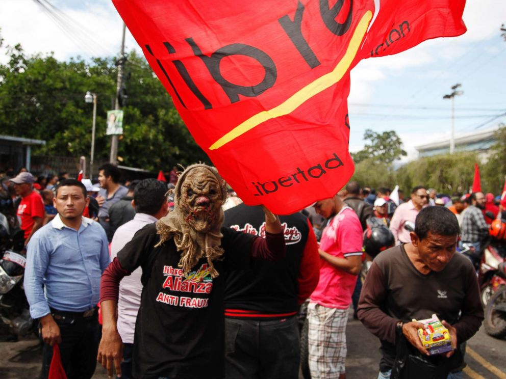 PHOTO: A supporter of Libre Alliance presidential candidate Salvador Nasralla wears a mask and holds a party banner during a protest march claiming electoral fraud, in Tegucigalpa, Honduras, Nov. 29, 2017.