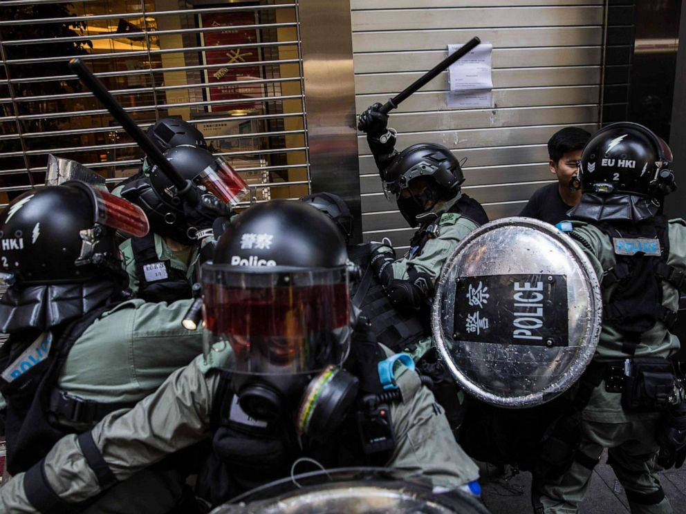 PHOTO: Riot police detain two men in the Central district of Hong Kong on November 11, 2019, as clashes ignited across the city and and crowds took to the streets to block roads and hurl insults at officers. (Photo by DALE DE LA REY/AFP via Getty Images)