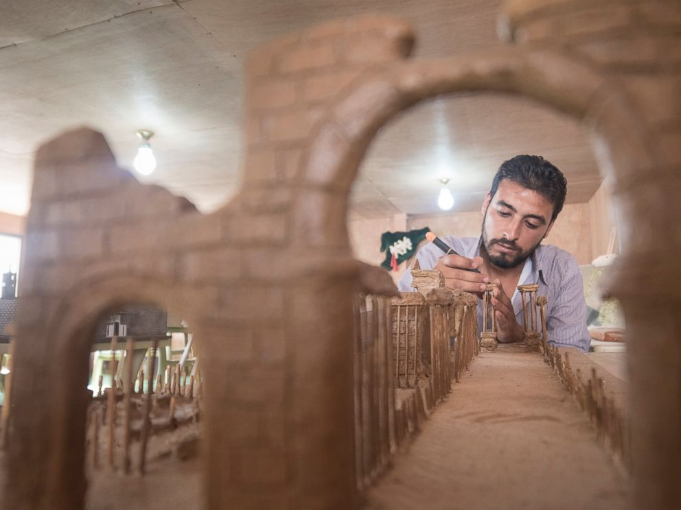 PHOTO: Mahmoud built his model of Palmyra using clay and wooden kebab skewers. Mahmoud hopes that by seeing the exhibition, residents at Zaatari will remain connected with the country and culture they have been forced to leave behind.