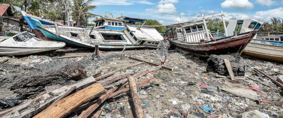 PHOTO: A resident passes by stranded boats among debris after a tsunami hit at Anyer in Banten, Indonesia, Dec. 24, 2018.