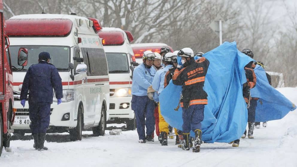 Rescuers carry people injured in an avalanche near a ski slope north of Tokyo, Japan, March 27, 2017.