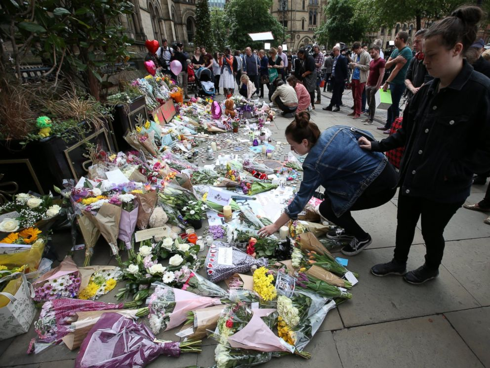 PHOTO: People at Albert Square in Manchester, UK look at the growing amount of floral tributes for the victims of the Manchester terror attack.