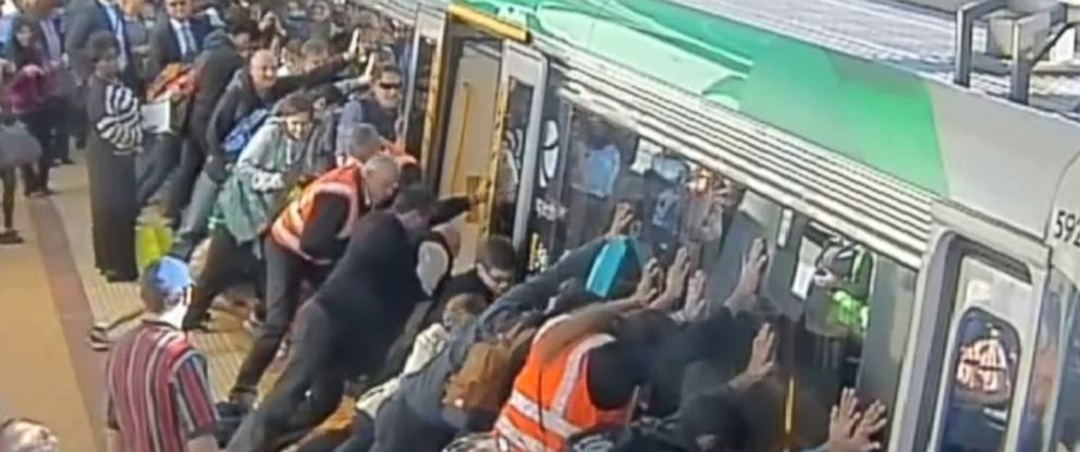 PHOTO: Passengers push against a train in Perth, Australia, Aug. 6, 2014, helping to free a man trapped between the train and platform.