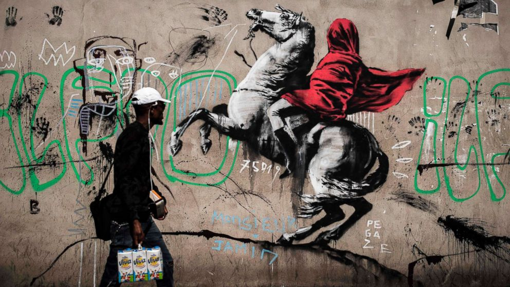 A man walks past a recent artwork by street artist Banksy in Paris on June 25, 2018. Anonymous street artist Banksy's artwork of Napoleon Bonaparte wearing a headscarf inspired by the original painting by Jacques-Louis David was found in northern Paris.