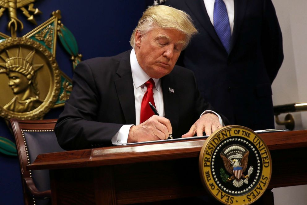 PHOTO: President Donald Trump signs an executive order to impose tighter vetting of travelers entering the United States, at the Pentagon, Jan. 27, 2017.