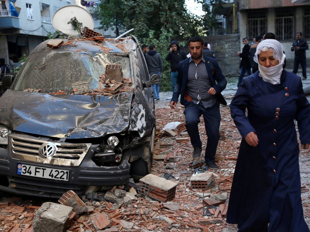 PHOTO: People walk past a damaged car after a blast in the Kurdish-dominated southeastern city of Diyarbakir, Turkey, Nov. 4, 2016.