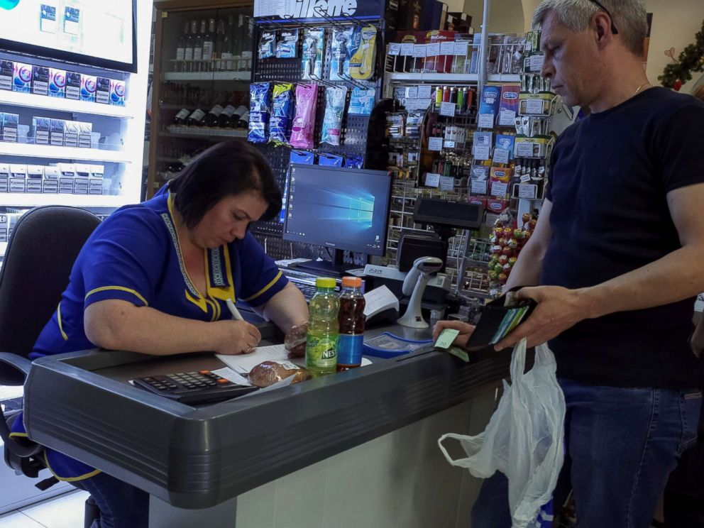 PHOTO: A customer at a store in Kiev, Ukraine, waits while a cashier writes out a purchase receipt for store records, as many business have turned off their digital cash registers after cases of cyber attacks on business, June 28, 2017.