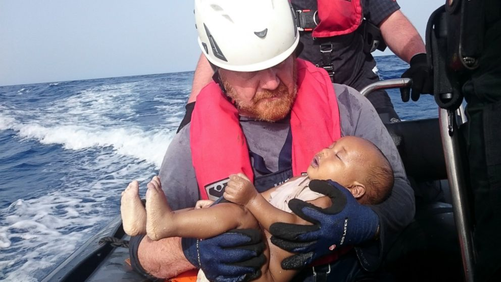German rescuer from the humanitarian organization Sea-Watch holds a drowned migrant baby, off the Libyan coast on May 27, 2016. The baby, who appears to be no more than a year old, was pulled from the sea after a wooden boat capsized last Friday.