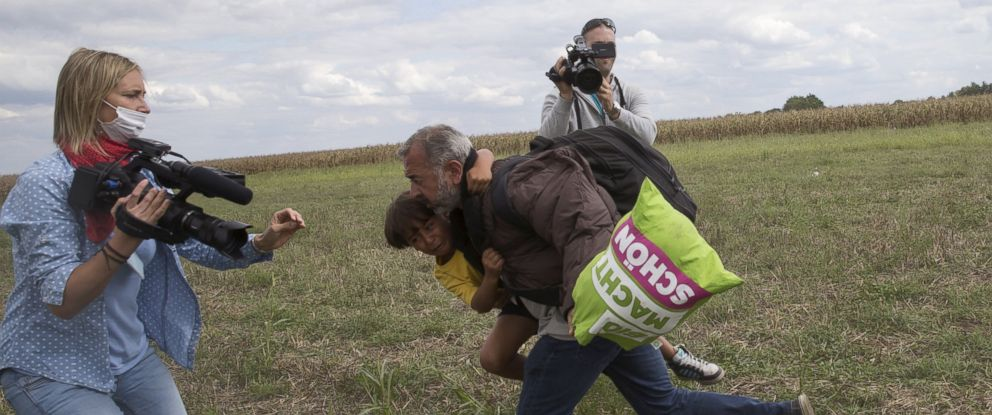 PHOTO: A Refugee runs with a child before tripping on TV camerawoman Petra Laszlo and falling as he tries to escape from a collection point in Roszke village, Hungary, Sept. 8, 2015.