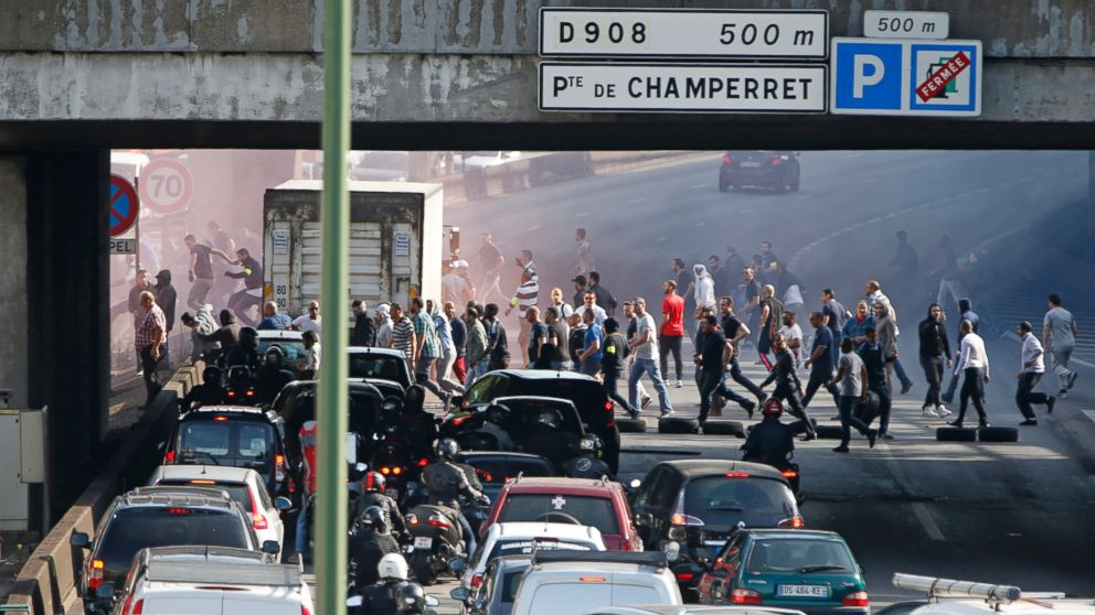 French taxi drivers, who are on strike, block the traffic on the Paris ring road during a national protest against car-sharing service Uber, in Paris, June 25, 2015.