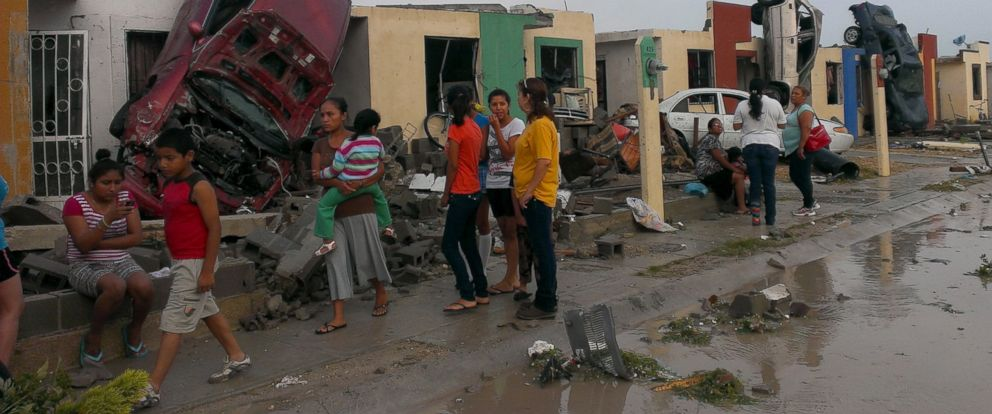 PHOTO: Residents stand outside their homes as damaged cars are seen after a tornado hit the town of Ciudad Acuna, state of Coahuila, May 25, 2015.