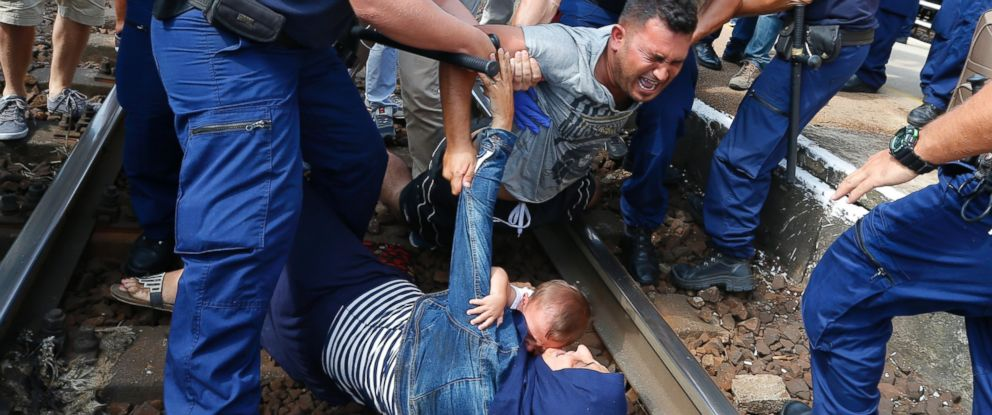 PHOTO: Hungarian policemen detain migrants on the tracks as they wanted to run away at the railway station in the town of Bicske, Hungary, Sept. 3, 2015.