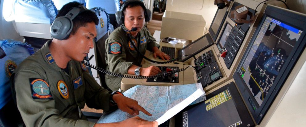 PHOTO: Two members of the Indonesian Navys Tactical Commanding Operator (TACCO) help with the search for AirAsia flight QZ8501 on board a CN235 aircraft over Karimun Java, in the Java Sea Dec. 28, 2014.