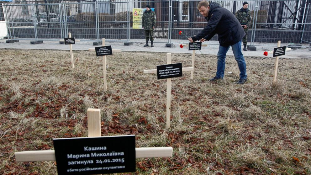 An activist places a cross with the name of a victim who was killed in shelling of the government-held port in Kiev, Feb. 1, 2015.