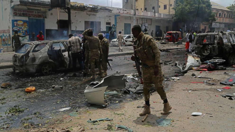 Somalian security forces inspect wreckage of a vehicle at the site after bomb-laden vehicle attack at Waberi district in Mogadishu, Somalia, June 30, 2017.