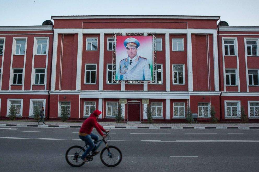 PHOTO: A cyclist rides past a banner featuring an image of Tajikistan President Emomali Rahmon displayed on a building in Dushanbe, Tajikistan, on April 22, 2018.