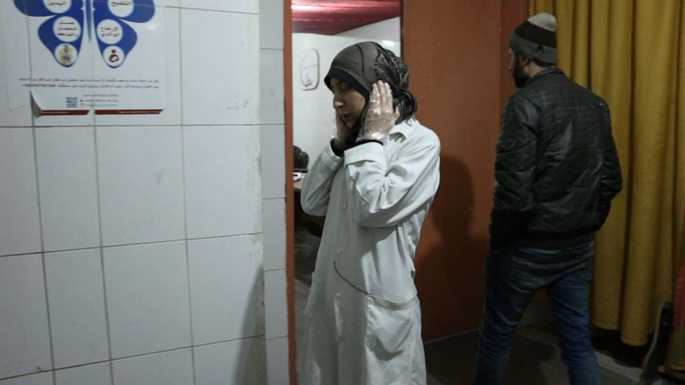 PHOTO: Dr Amani covers her ears during nearby bombings, in Al Ghouta, Syria.