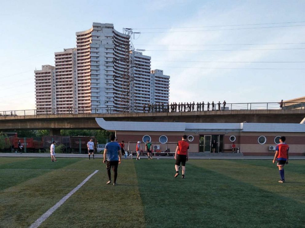 PHOTO: North Korean soldiers watch from an overpass as a group of foreigners play soccer on a field on Tongil Street, Pyongyang, North Korea, May 19, 2018.
