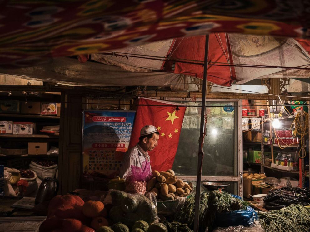 PHOTO: An ethnic Uyghur shopkeeper works next to a Chinese flag at his shop, June 29, 2017, in the old town of Kashgar, in the far western Xinjiang province, China.