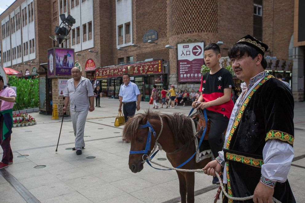 PHOTO: A Han boy rides a donkey own by a Uyghur at the Xinjiang International Grand Bazaar in Urumqi, capital of northwest Chinas Xinjiang Uyghur Autonomous Region in China, July 2, 2017.