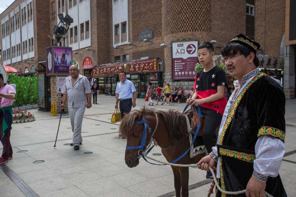 PHOTO: A Han boy rides a donkey own by a Uyghur at the Xinjiang International Grand Bazaar in Urumqi, capital of northwest Chinas Xinjiang Uyghur Autonomous Region in China, July 2, 2017.