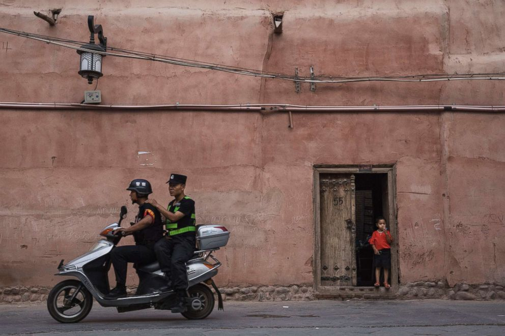 PHOTO: Police patrol on a scooter as an ethnic Uyghur boy stands in his doorway,June 27, 2017, in the old town of Kashgar, in the far western Xinjiang province, China.