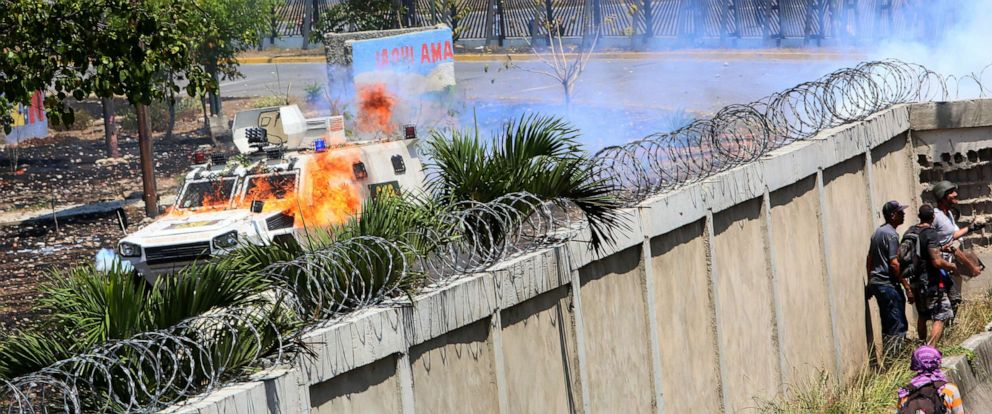 PHOTO:Demonstrators throw petrol bombs to military forces at the air force base La Carlota, April 30, 2019, in Caracas, Venezuela.