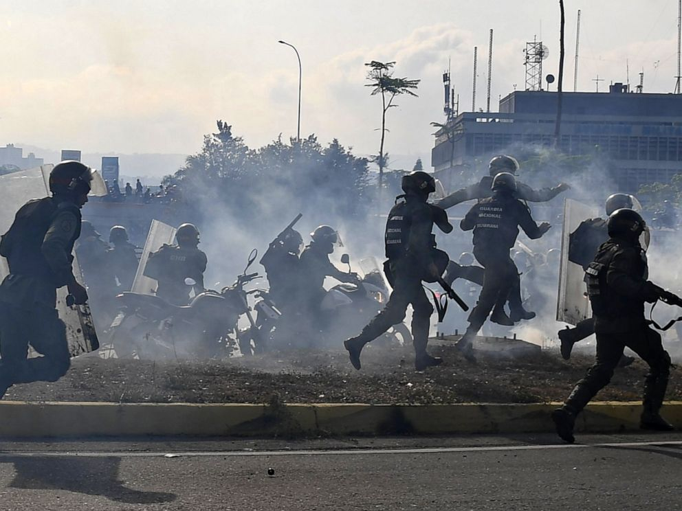 PHOTO: Members of the Bolivarian National Guard loyal to Venezuelan President Nicolas Maduro run under a cloud of tear gas after being repelled with rifle fire by guards supporting Venezuelan opposition leader Juan Guaido in Caracas, April 30, 2019.