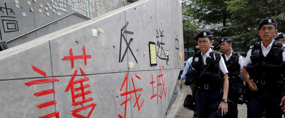 """Hong Kong police officers pass by words formed with tape which read """"Protect our city, against extradition to China"""" near the Legislative Council in Hong Kong on Friday, June 14, 2019. Calm appeared to have returned to Hong Kong after days of protest"""
