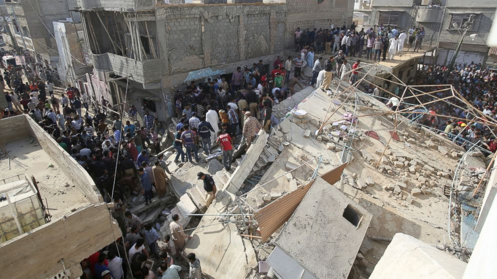 People gather near a collapsed building while rescue work is in progress in Karachi, Pakistan, Monday, Feb. 25, 2019. The small residential building collapsed as construction work was underway next to it in the city's Malir neighborhood. (AP Photo/Fareed Khan)