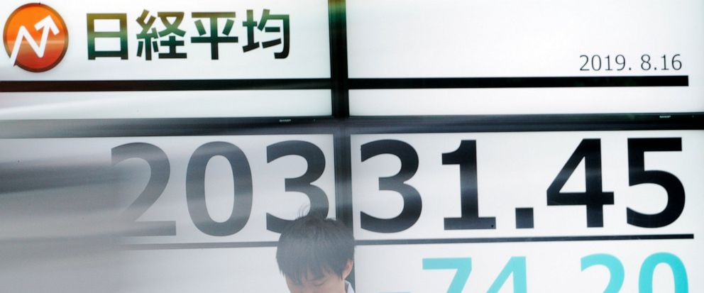 A man stands as a car goes by an electronic stock board showing Japans Nikkei 225 index at a securities firm in Tokyo Friday, Aug. 16, 2019. Asian shares were mixed Friday as turbulence continued on global markets amid ongoing worries about U.S.-Chi