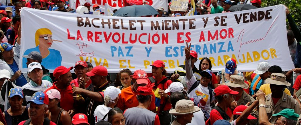 "Supporters of President Nicolas Maduro holds up a banner with a message that reads in Spanish: ""Bachelet lies and sold herself. The revolution is love, peace and hope,"" during a protest against a report by Michelle Bachelet, U.N. high commissioner fo"