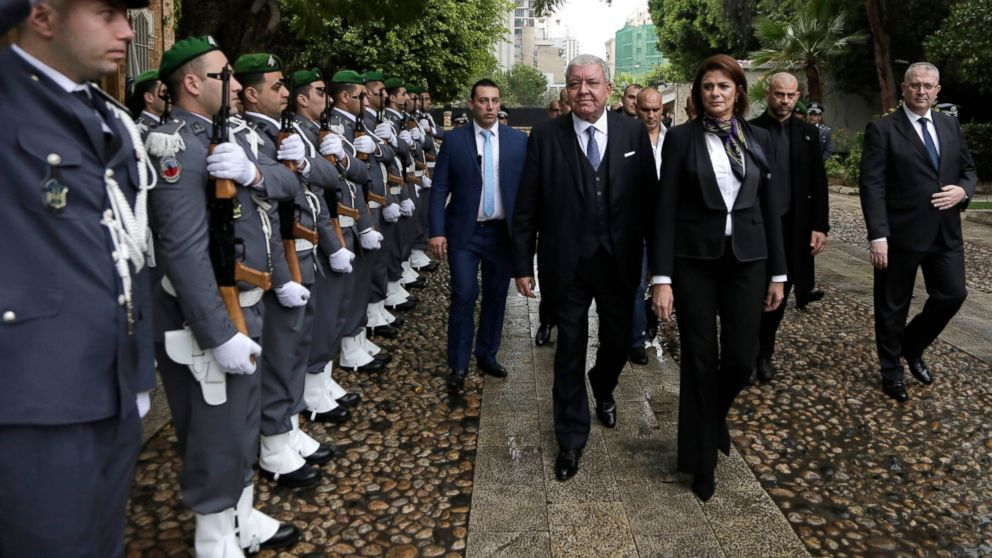 Newly appointed Interior Minister Raya El Hassan, third right, and former Lebanese Interior Minister Nohad Machnouk, center, review an honor guard during a ceremony at the interior ministry in Beirut, Lebanon, Wednesday, Feb. 6, 2019. El Hassan is one of four women in the new 30-member Cabinet, becoming the country and the Arab world's first female official in charge of the powerful security agencies. (AP Photo/Hassan Ammar)