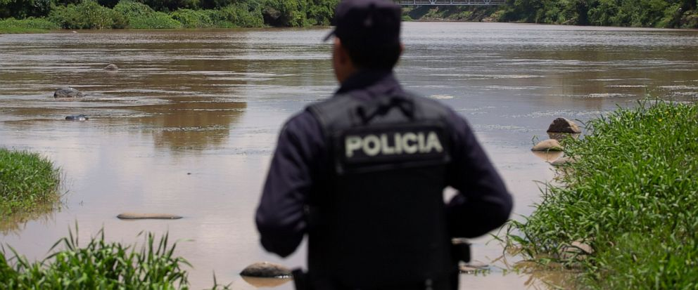 An El Salvadoran national police agent looks out over La Paz River on the border with Guatemala in La Hachadura, El Salvador, Thursday, Sept. 12, 2019, as part of a deployment of 800 police and soldiers to patrol blind spots along its borders where m