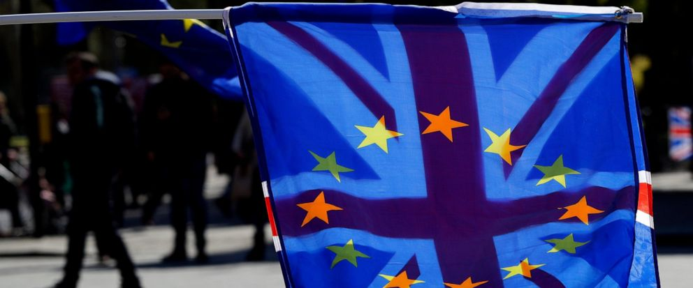 A British Union flag is flown behind a European Union flag during demonstrations near Parliament in London, Wednesday, April 10, 2019. Just days away from a no-deal Brexit, European Union leaders meet Wednesday to discuss granting the United Kingdom