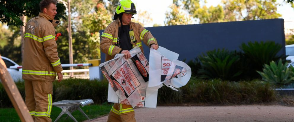 A fire fighter is seen carrying a hazardous material bag into the Korean consulate in Melbourne, Wednesday, Jan. 9, 2019. Several foreign consulates in Melbourne were evacuated Wednesday as Australian officials noted they were responding to multiple