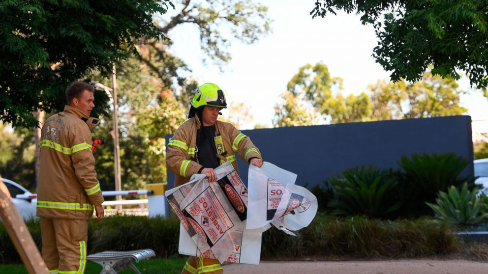 "A fire fighter is seen carrying a hazardous material bag into the Korean consulate in Melbourne, Wednesday, Jan. 9, 2019. Several foreign consulates in Melbourne were evacuated Wednesday as Australian officials noted they were responding to multiple ""hazardous material"" events in the city. (James Ross/AAP Image via AP)"