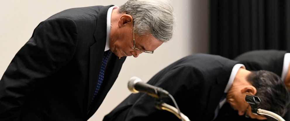 Kansai Electric Power Co. Chairman Makoto Yagi, left, bows in apology at the beginning of a press conference in Osaka, western Japan Wednesday, Oct. 9, 2019. Yagi has resigned over a scandal involving 20 of its executives who received cash and lavish