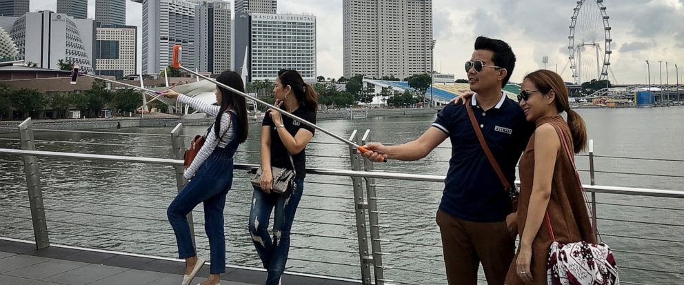 FILE - In this Jan. 20, 2016, file photo, tourists use selfie sticks to take photos of themselves with their smart phones at one of Singapores popular tourists spots with the financial skyline and hotels in the background in Singapore. The World Eco