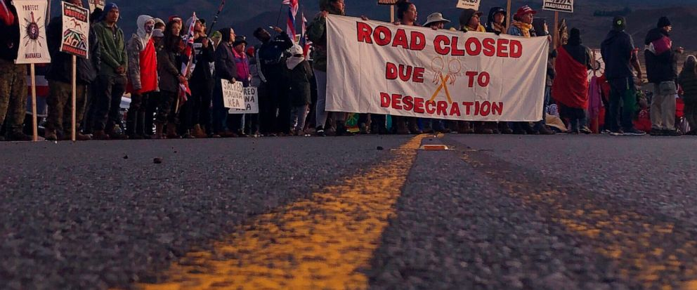 FILE - In this July 15, 2019, file photo, demonstrators block a road at the base of Hawaiis tallest mountain, in Mauna Kea, Hawaii, to protest the construction of a giant telescope on land that some Native Hawaiians consider sacred. The University o