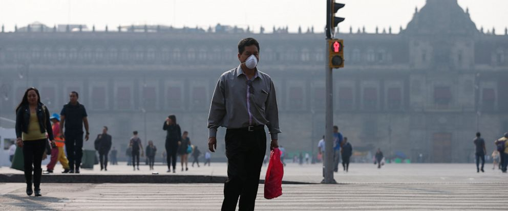 A man wearing a face mask crosses a street backdropped by the National Palace shrouded by haze, in the Zocalo, Mexico Citys main square, Thursday, May 16, 2019. A siege of air pollution blanketing the capital has led to school closures and the cance