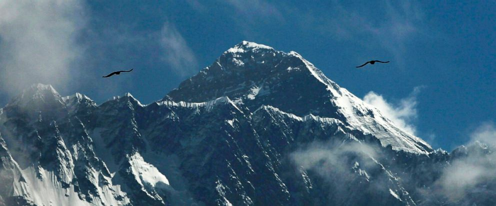 FILE - In this May 27, 2019, file photo, birds fly as Mount Everest is seen from Namche Bajar, Solukhumbu district, Nepal. A Nepal government committee formed after a bad mountaineering season on Mount Everest has recommended new rules that would req