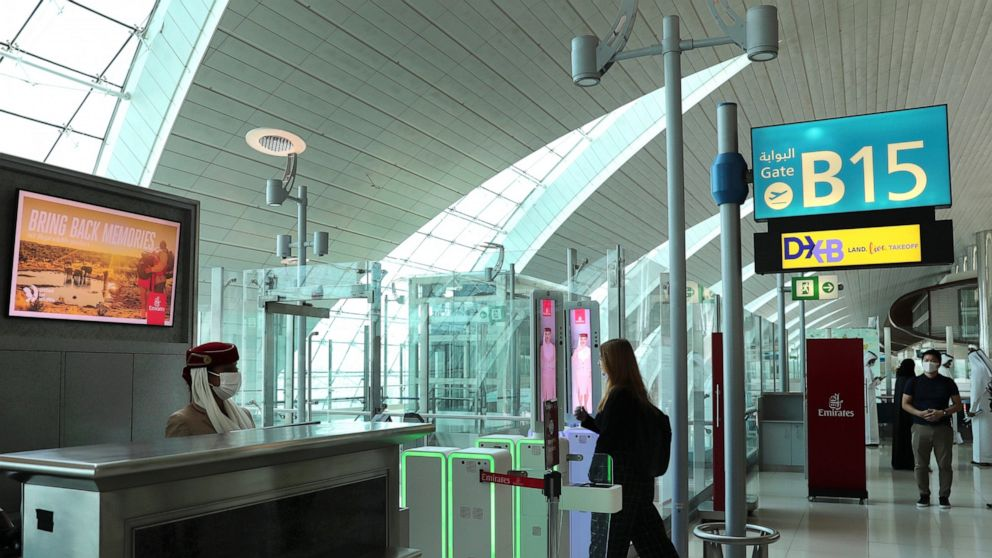 A woman enters the face and iris-recognition gate to board a plane, during a media tour at Dubai Airport, in the United Arab Emirates, Sunday, March 7, 2021. Dubai's airport, the world's busiest for international travel, has introduced an iris-scanne