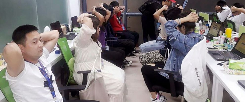 In this Oct. 9, 2019, photo provided by Philippine Bureau of Immigration, foreign nationals, mostly Chinese put their hands on their heads during a raid of their company premises in Manila, Philippines. Philippine police and immigration authorities s